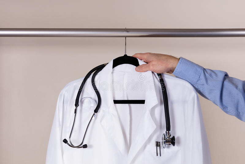 Manteau blanc médical de consultation avec le stéthoscope étant enlevé photographie stock