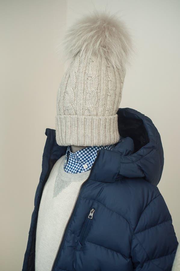 Manteau d'hiver et chapeau bleus de laine sur le mannequin dans la salle d'exposition de magasin de mode image libre de droits