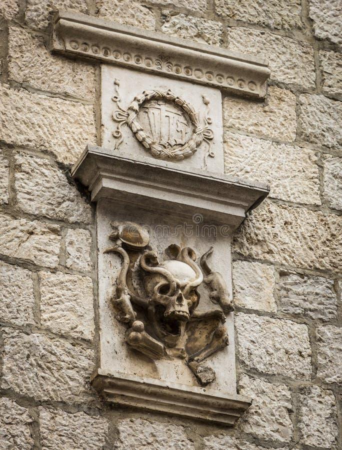 Manteau de famille des bras antique sous forme de crâne avec des serpents sur le mur d'un vieux bâtiment dans la ville de Kotor,  photos libres de droits