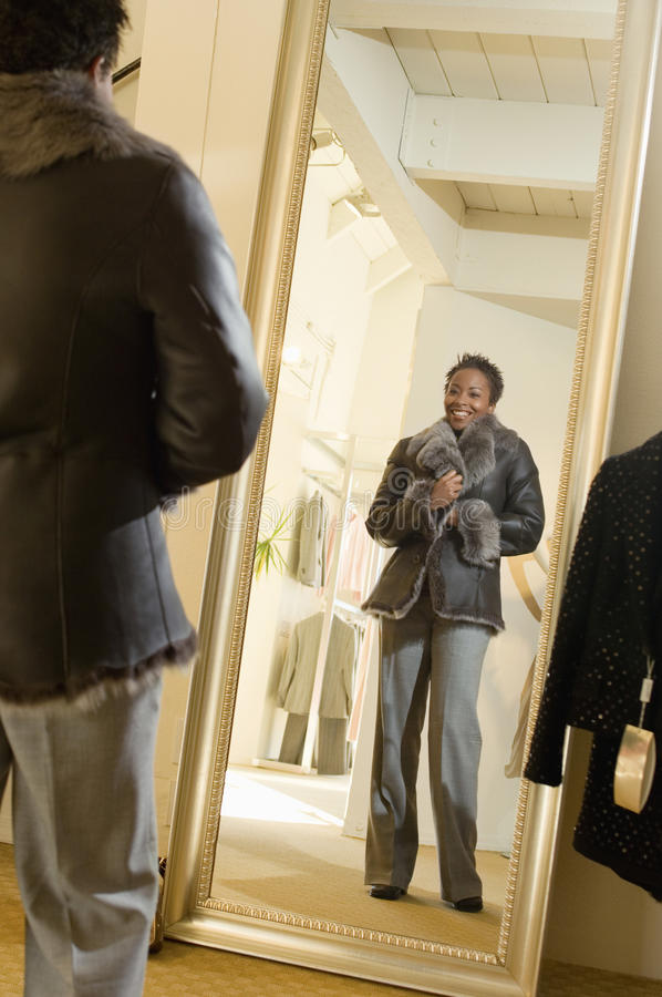 Manteau de fourrure de essai de femme à la boutique image stock