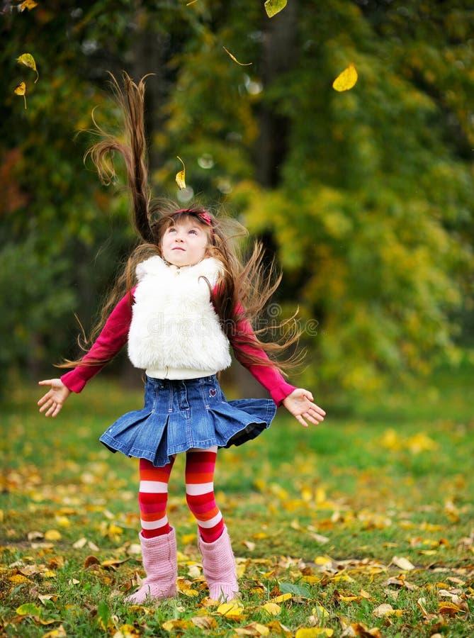 Manteau de fourrure s'usant mignon de petite fille dans la forêt d'automne photos stock