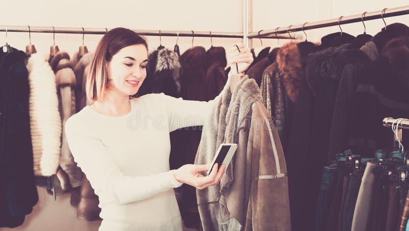 Manteau de peau de mouton de examen de gentil client féminin photos libres de droits
