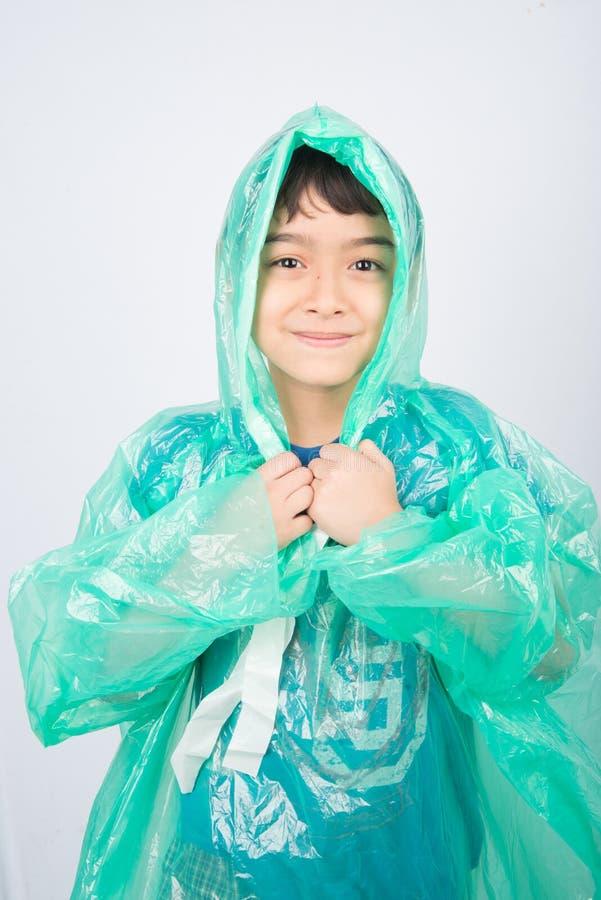 Manteau de pluie de port de petit garçon sur le fond blanc image stock