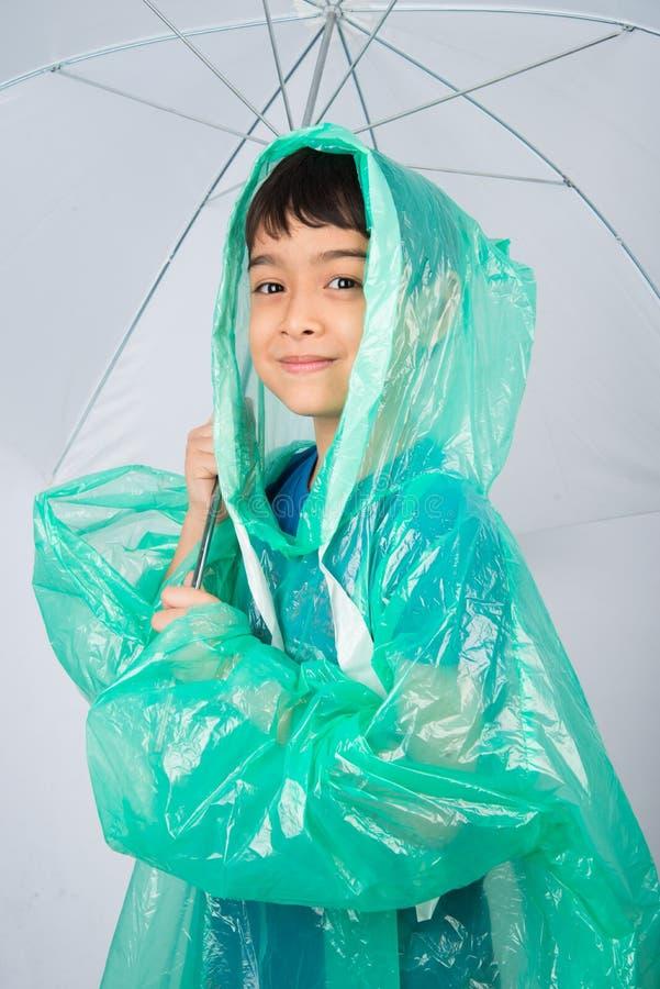Manteau de pluie de port de petit garçon sur le fond blanc photo libre de droits
