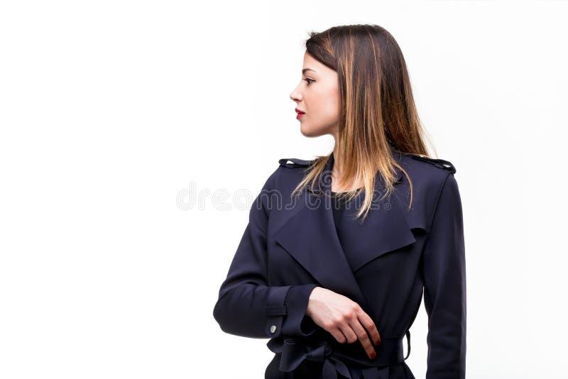 Manteau de port de jeune femme sur le fond blanc images libres de droits