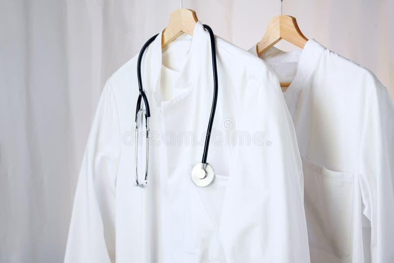 Manteaux blancs de laboratoire de médecin ou de médecin avec le stéthoscope accrochant sur des cintres, l'espace de copie photos libres de droits