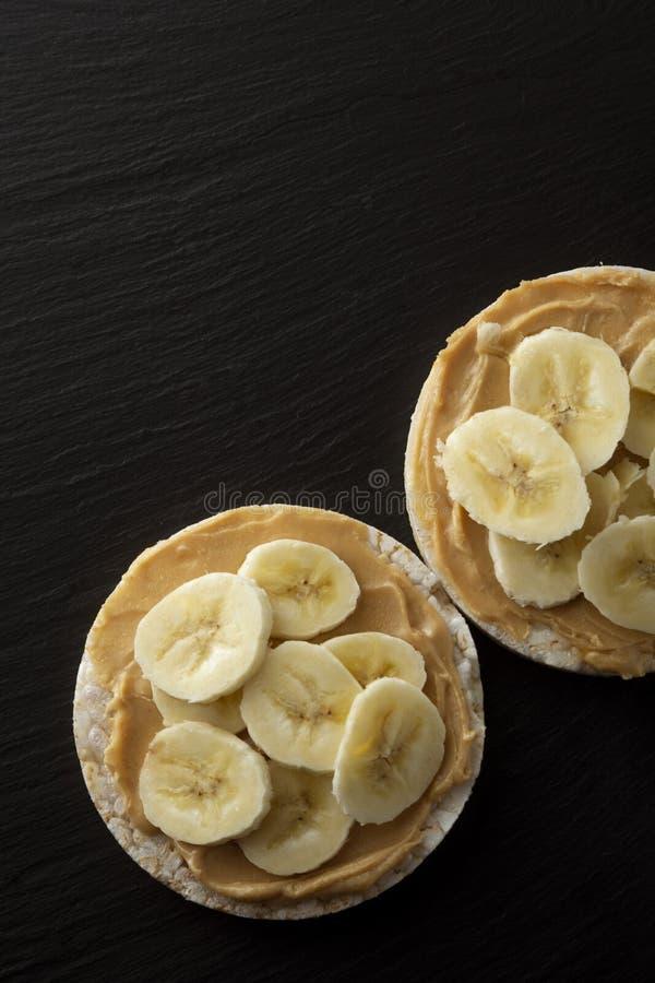 Manteiga de amendoim e banana em bolos de arroz, alimento saud?vel, diet?tico Fundo preto foto de stock