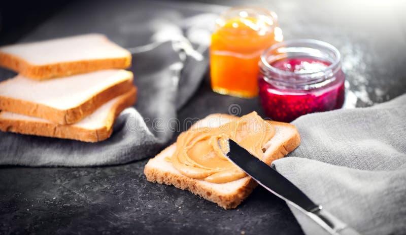 Manteiga de amendoim Fazendo sanduíches com manteiga e geleia de amendoim Nutrição natural e alimento saudável foto de stock