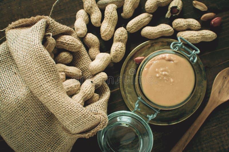 Manteiga de amendoim orgânica no frasco de vidro com os amendoins em Shell no fundo de madeira foto de stock royalty free