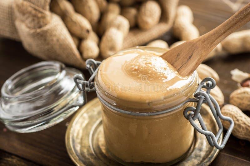 Manteiga de amendoim orgânica no frasco de vidro com os amendoins em Shell no fundo de madeira imagem de stock