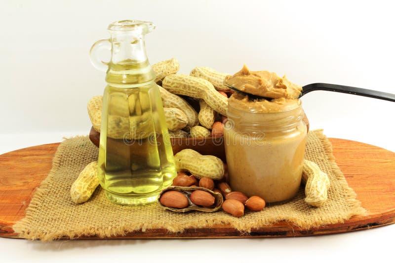 Manteiga e amendoins de amendoim inteiros e descascados com óleo de amendoim foto de stock