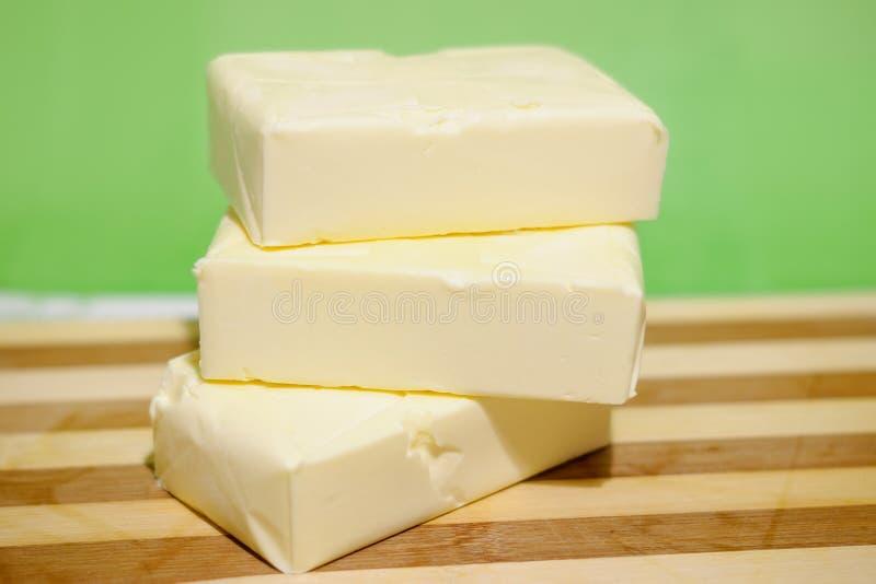 Manteiga nos carvões amassados em uma placa de desbastamento foto de stock