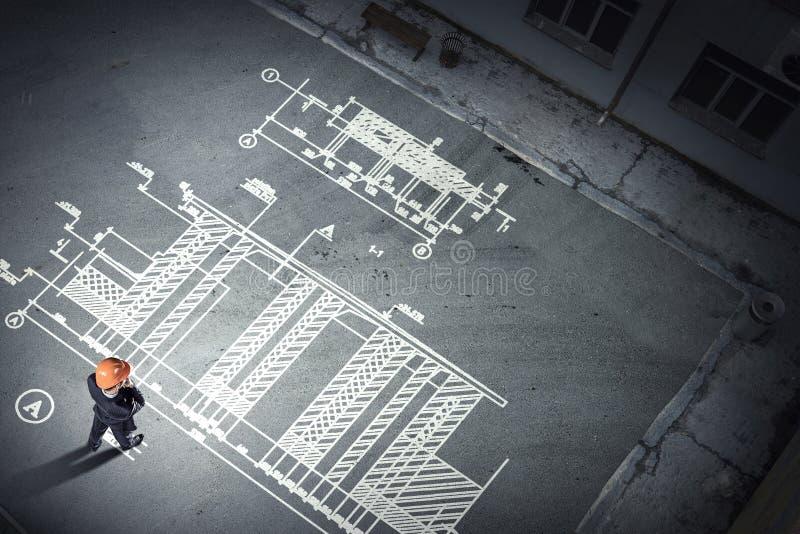 Mantekniker som tänker över hans plan Blandat massmedia royaltyfri foto