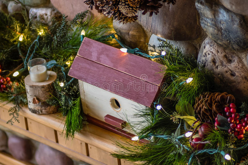 Mantel decorated for Christmas with lights. A wooden mantel decorated with greens and a wooden bird house royalty free stock photos