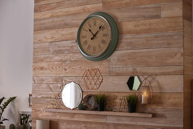 Mantel shelf with stylish interior decorations. On wooden wall stock images
