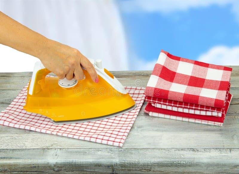 Manteles que planchan de la mujer en la tabla gris rústica con un blanco azul fotografía de archivo libre de regalías