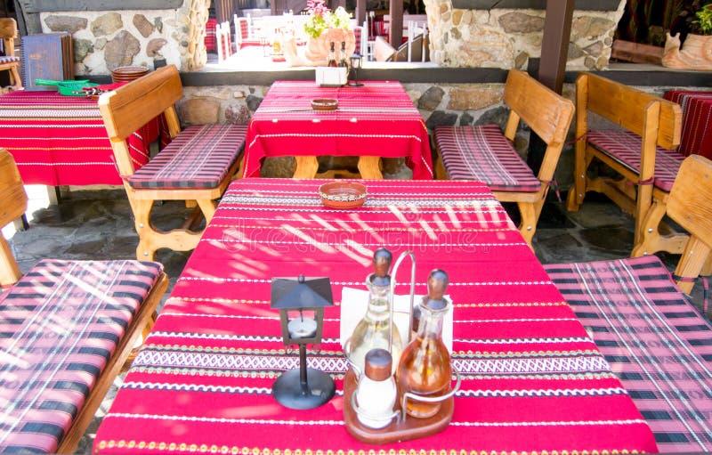 Manteles rojos tradicionales coloridos en las tablas y los bancos de madera imagen de archivo