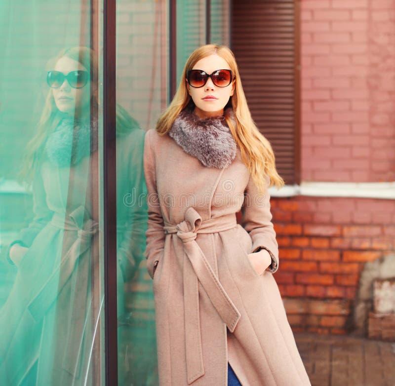 Manteljacke und -Sonnenbrille der schönen eleganten Blondine des Porträts tragende in der Stadt lizenzfreie stockbilder