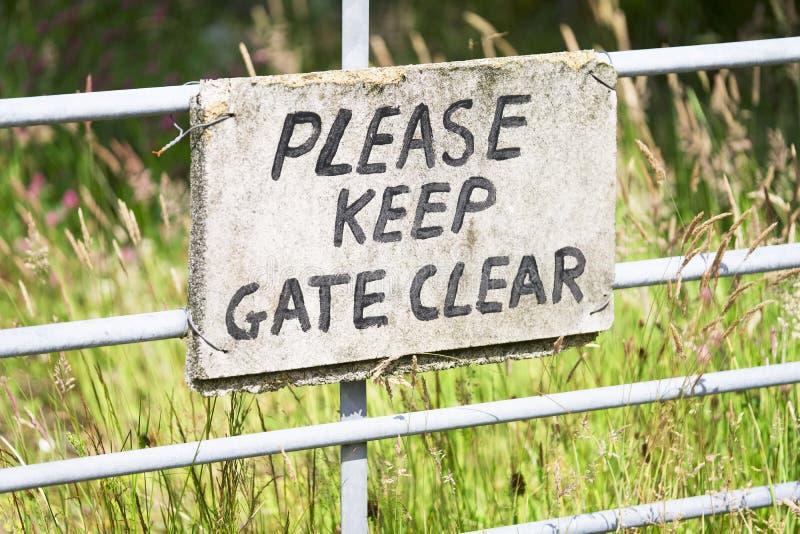 Mantenga por favor la muestra del claro de la puerta cerca de la puerta del metal imágenes de archivo libres de regalías