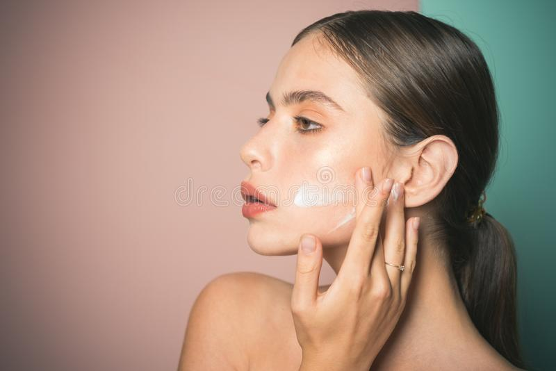 Mantenha a pele hidratou o creme regularmente hidratando Tomando bom de sua pele Creme de espalhamento da mulher bonita nela imagem de stock royalty free