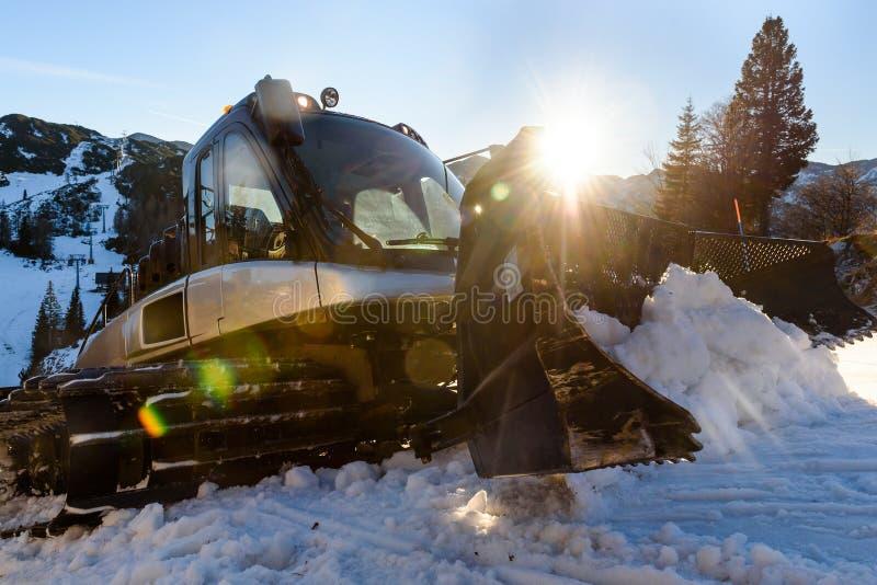 Mantenimiento de las cuestas del esquí de Snowcat del quitanieves en las montañas fotografía de archivo