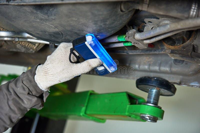 Mantenimiento del acondicionador de aire del coche escape de freón de la detección con la lámpara ultravioleta fotos de archivo libres de regalías