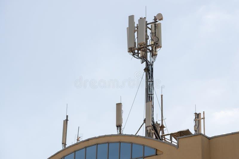 Mantenimiento del técnico en la torre de la telecomunicación que hace control ordinario del mantenimiento a una antena para la co fotos de archivo