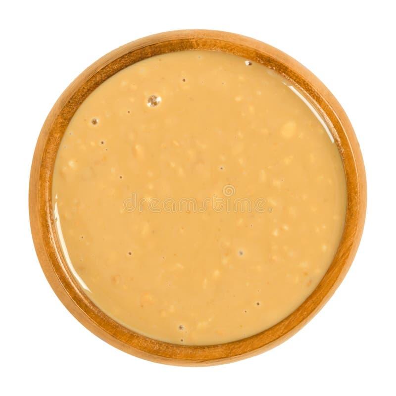 Mantequilla de cacahuete crujiente en cuenco de madera sobre blanco imagen de archivo libre de regalías