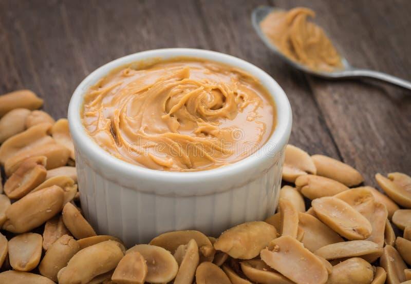 Mantequilla de cacahuete en cuenco y cacahuetes fotos de archivo libres de regalías