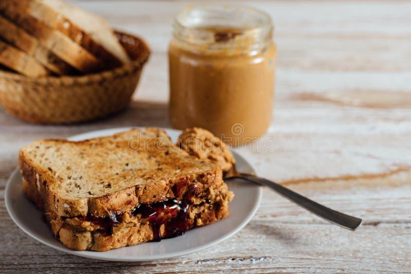 Mantequilla de cacahuete y bocadillo hechos en casa de la jalea en fondo de madera foto de archivo