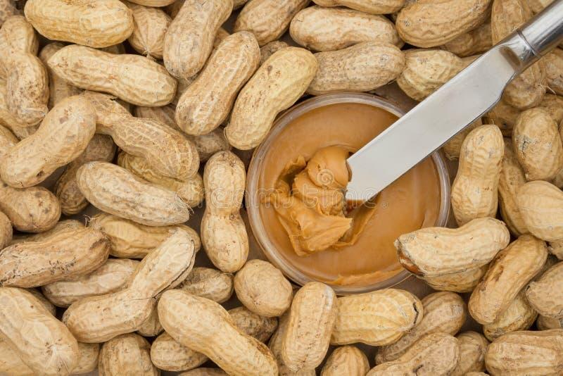 Mantequilla de cacahuete y cacahuetes crudos en cáscaras fotos de archivo