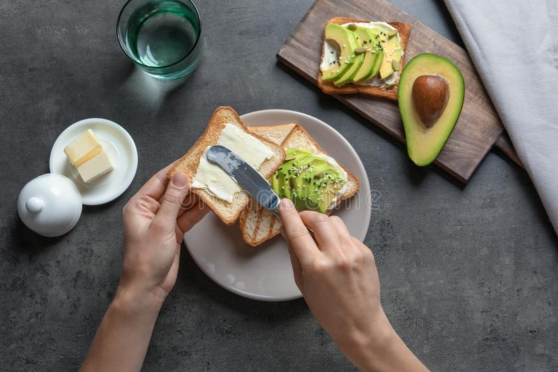 Mantequilla de extensión de la mujer en el pan tostado imagen de archivo libre de regalías