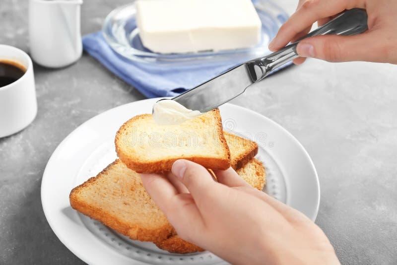 Mantequilla de extensión de la mujer en el pan tostado en la tabla imagen de archivo