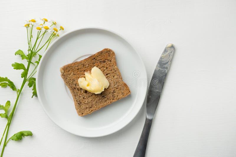 Mantequilla en la tostada para el desayuno foto de archivo