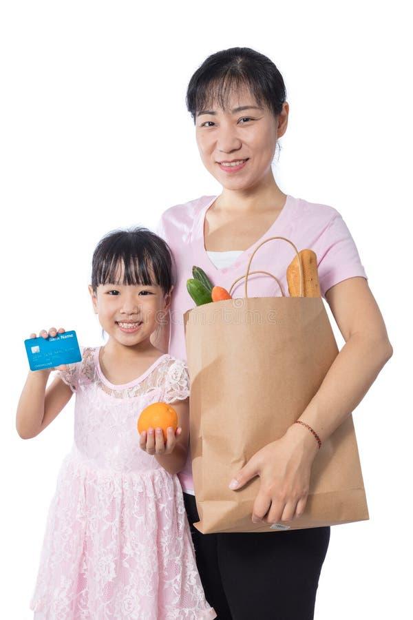Mantimentos de compra asiáticos da mulher e da filha com cartão de crédito foto de stock