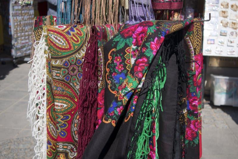 Mantones polacos y rusos multicolores nacionales tradicionales para la venta en la tienda de souvenirs para los turistas imágenes de archivo libres de regalías