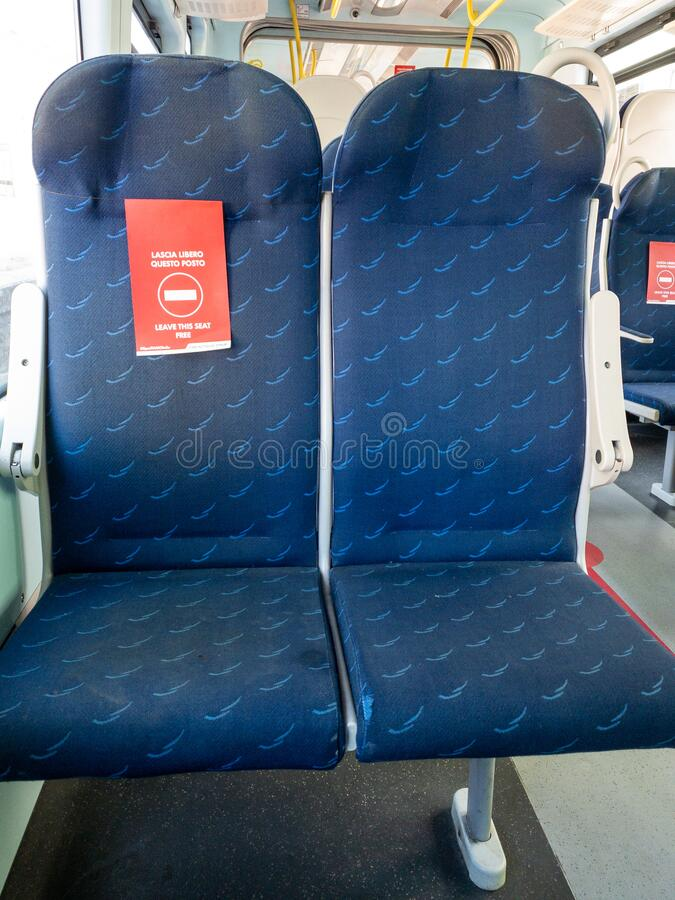 Mantova, Italy - 20th June 2020: trenitalia train seats with a red sign that says to leave seat free. New distancing rules due to coronavirus pandemic stock image
