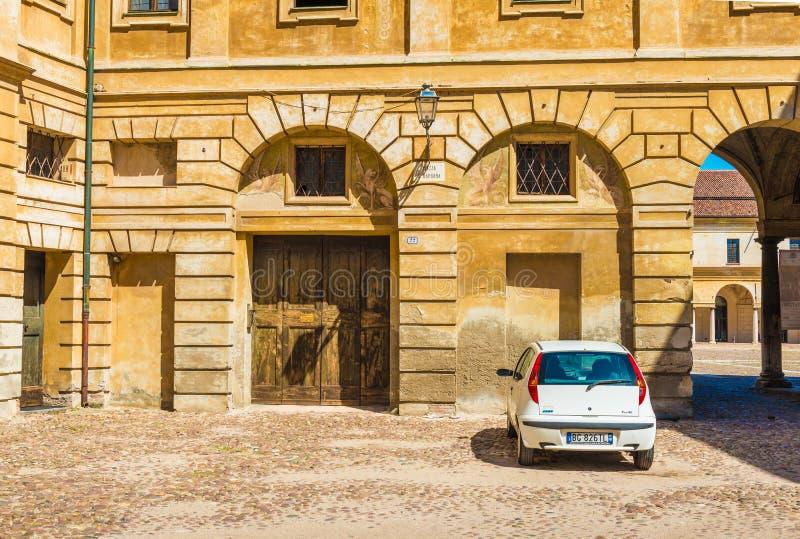 Mantova Mantua, Italien: Liten vit bil som parkeras nära den historiska byggnaden fotografering för bildbyråer