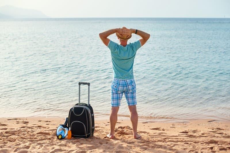Manturist i sommarkläder med en resväska i hans hand som ser havet på stranden, begrepp av tid att resa royaltyfria foton