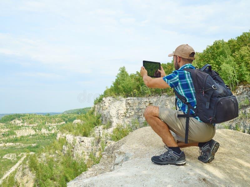 Manturisten använder minnestavladatorsammanträde på kanten av klippan i mou royaltyfri foto