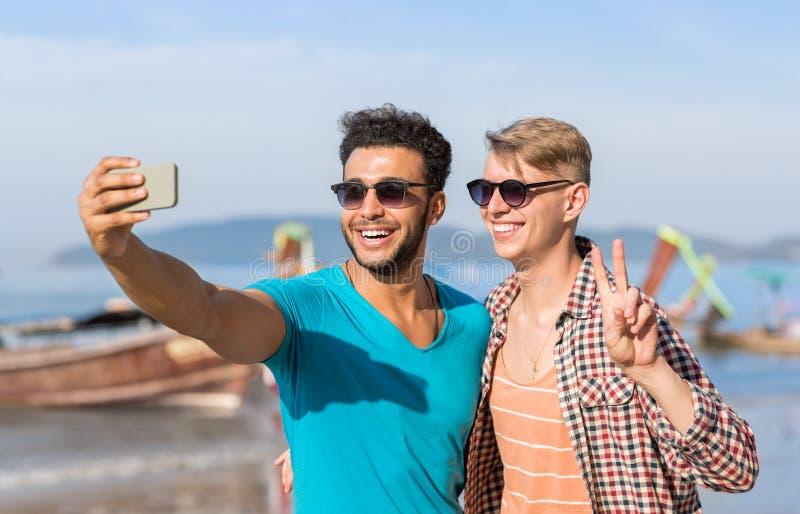 Manturistpar som tar det Selfie fotoet i Front Of Long Tail Boat på stranden på den cellSmart telefonen, två lyckliga unga grabba arkivbild