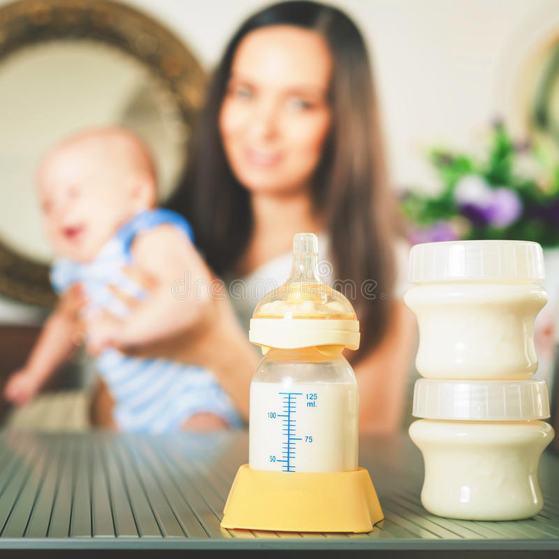 Manual breast pump, mothers breast milk. Is the most healthy food for newborn baby. Happy mother with infant at background at the kitchen royalty free stock image