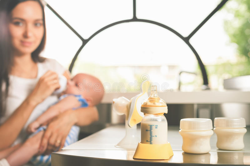 Manual breast pump, mothers milk. Manual breast pump, mothers breast milk is the most healthy food for newborn baby. Happy mother with infant at background at stock images