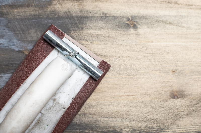 Manual carpentry holder for sandpaper lies on the sanding surface of an old wooden black table. Home repairs. Close-up stock photos