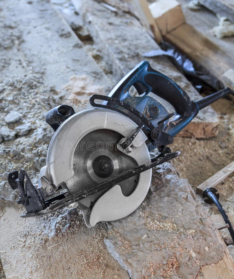manual circular saw is on a wooden board in house under construction of foam block royalty free stock photo