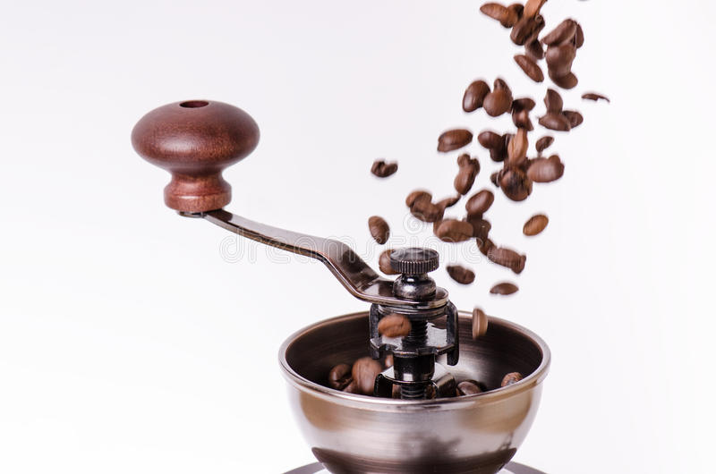 Manual coffee grinder with coffee beans. Isolated. White background. Modern style. Roasted coffee beans. Levitation coffee beans.  royalty free stock image