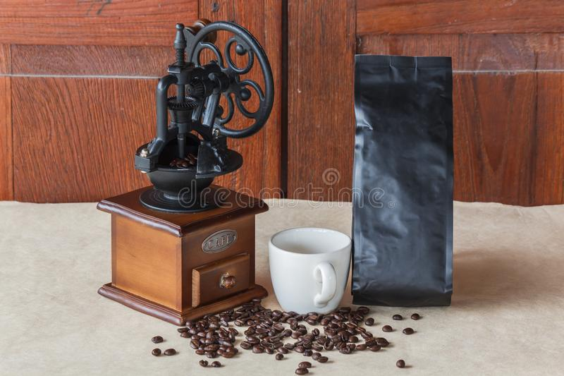 Manual coffee grinder with cup coffee and black coffee beans with coffee bag on recycle paper royalty free stock images
