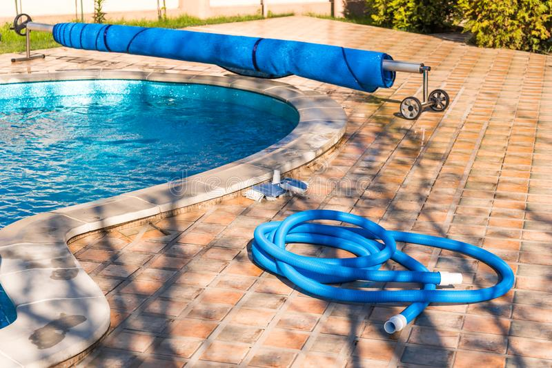 Manual equipment for cleaning pool, brush, hose, swimming pool cover, Yesulskaya, Krasnodar, Russia. Copy space for text. royalty free stock image