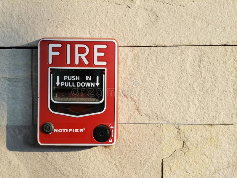 Manual fire alarm On the white stone tile wall stock image