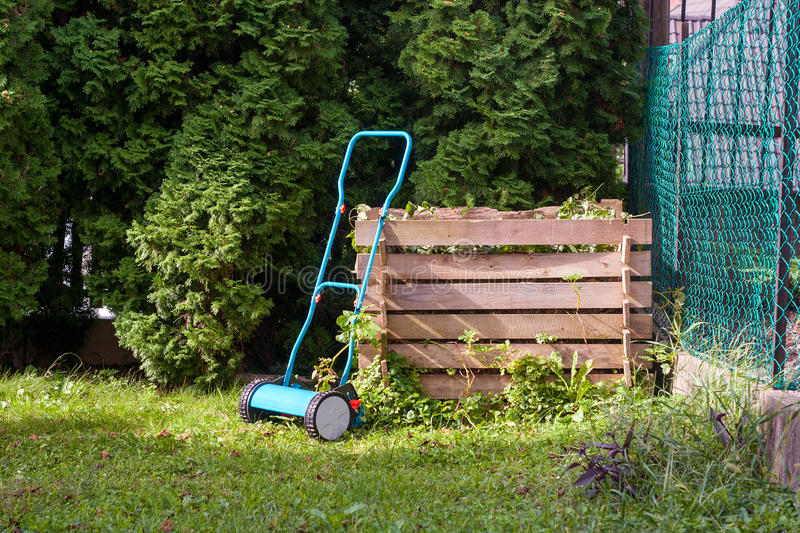 Manual lawn mower. At a wooden compost bin royalty free stock photo